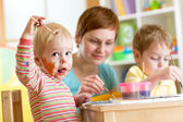 Mother and little boys messily playing with paints — Stock Photo