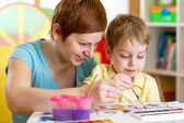 Mom and kid boy paint together at home — Stock Photo