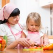 Mother and kid girl cooking and cutting vegetables on kitchen — Stock Photo #63037041