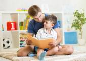 Kid and his father read a book — Stock Photo
