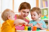 Woman and children playing with paints — Stock Photo