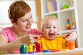 Mother and toddler boy paint together at home — Stock Photo