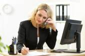 Businesswoman working in office. Employee talking by phone and writing by pen — Stock Photo