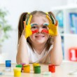 Cute kid girl showing her hands painted in bright colors — Stock Photo #63741503