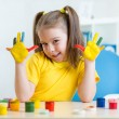 Kid girl showing painted hands — Stock Photo #63741789