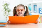 Happy funny child girl in glasses reading a book in primary school — Stockfoto