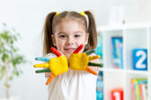 Little girl with hands in paint on nursery background — Fotografia Stock