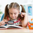 Cute kid looking through a magnifying glass with book — Stock Photo #63986011