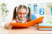 Happy funny child girl in glasses reading a book — Foto de Stock