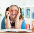 Cute little girl reading a book while wearing glasses — Stock Photo #64700593