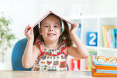 Student child with a book over her head — Foto de Stock