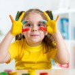 Cute child have fun painting her hands — Stock Photo #64900879