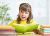 Cute little girl reading story from big book in nursery — Stock Photo