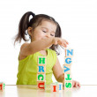 Little girl playing with wooden blocks with letters — Stock Photo #65621705