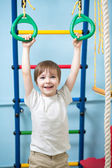 Child hanging on gymnastic rings — Stock Photo