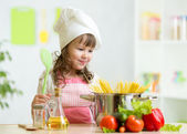 Cook kid makes healthy vegetables meal in the kitchen — Stock Photo