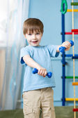 Strong kid exercising with dumbbells — Stock Photo