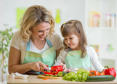 Mom and her daughter preparing vegetables at kitchen — Stock Photo