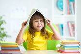 Smiling child with a book over her head — Stock Photo