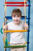 Kid boy climbing a rope ladder — Stock Photo