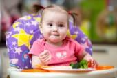 Kid eating food on kitchen — Stock Photo
