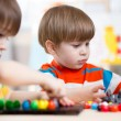 Two kids brothers play together at table — Stock Photo #66177903