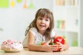 Child choosing  healthy vegetables instead of sweet cake — Stockfoto