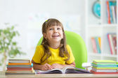 Smiling child girl reading book at home — Stock Photo