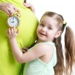 Child looks at alarm clock and pregnant woman belly — Stock Photo #67170711
