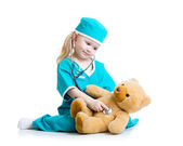 Adorable child with clothes of doctor examining  bear toy — Stock Photo