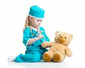 Child girl with clothes of doctor playing toy — Photo