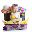 Baby girl sitting in suitcase with things for vacation travel — Stock Photo #68128559