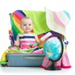 Baby girl sitting in suitcase with things for vacation travel — Stock Photo #69276369