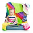 Baby girl sitting in suitcase with things for vacation travel — Stock Photo #69425673