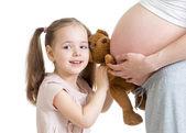 Счастливый ребенок девочка, играя с беременной матери — Стоковое фото