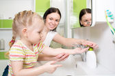 Happy kid with mom washing hands in bathroom — Стоковое фото