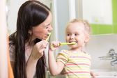 Cute mom teaching child teeth brushing — Stock Photo