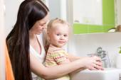 Happy mother and daughter washing hands at home in bathroom — Stock Photo