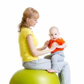 Mother doing gymnastics with baby on fitness ball — Stock Photo