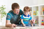 Kid boy and his dad read a book — Stock Photo