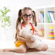 Child girl playing doctor and curing plush toy — Stock Photo #70734745