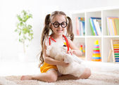 Child girl playing doctor and curing plush toy — Stock Photo