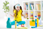 Frustrated kid sitting on floor with cleaning tools — Stock Photo