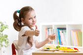 Child eats healthy food showing thumb up — Stock Photo