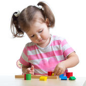 Little child girl playing with puzzle toys — Stock Photo