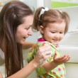 Smiling girl child and her mom washing hands and face with soap in the bathroom. Hygiene. — Stock Photo #72455349
