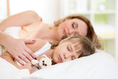 Child with mother preparing for napping on bed — Stock Photo