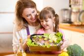 Mother and child jolly look at prepared dish of fish — Stock Photo