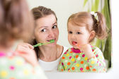 Woman teaching child daughter teeth brushing in bathroom. — Stock Photo