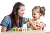Little girl together with mother playing cubes toys — Stock Photo